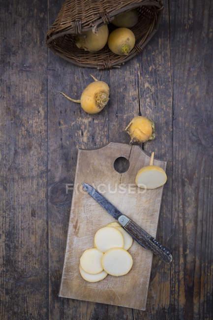 Cesta de vime com nabo Sueco inteiro e fatiado, placa de madeira e uma faca em madeira escura — Fotografia de Stock
