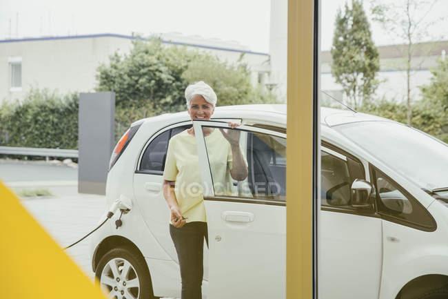 Mature woman charging electric car — Stock Photo