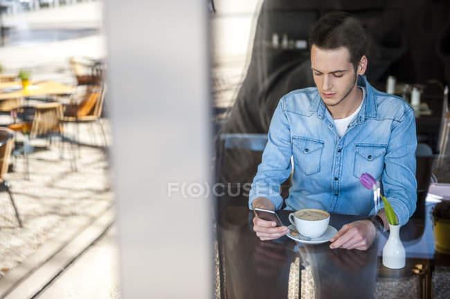 Giovane in café controllo cellulare — Foto stock