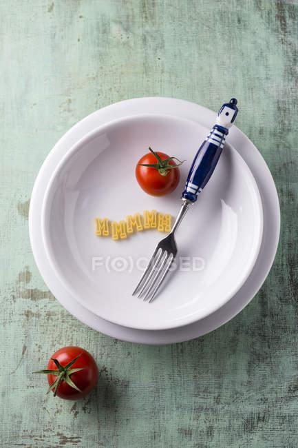 Tomate, letras de massa e um garfo no prato — Fotografia de Stock