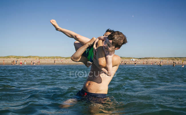 Playful father and son having fun in sea — Stock Photo