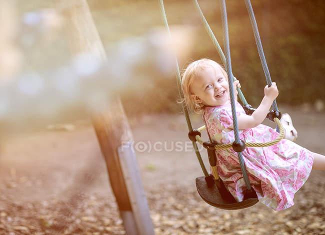 Portrait de fillette blonde vêtue de robe avec dessin floral assis sur une balançoire — Photo de stock