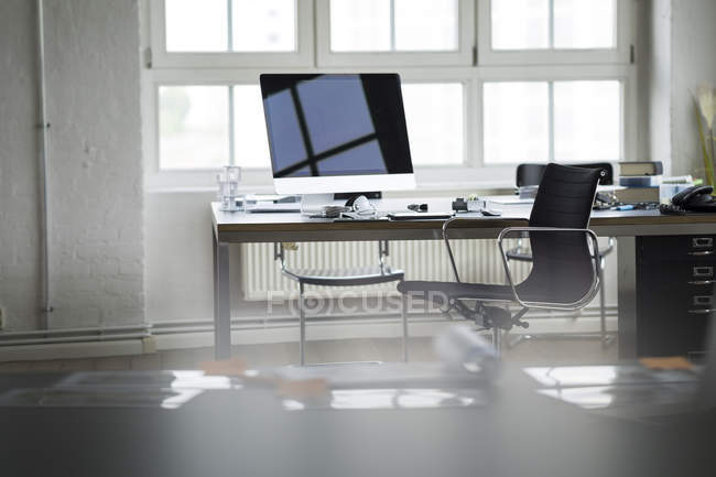 Desk, computer and chair in bright office interior — Stock Photo