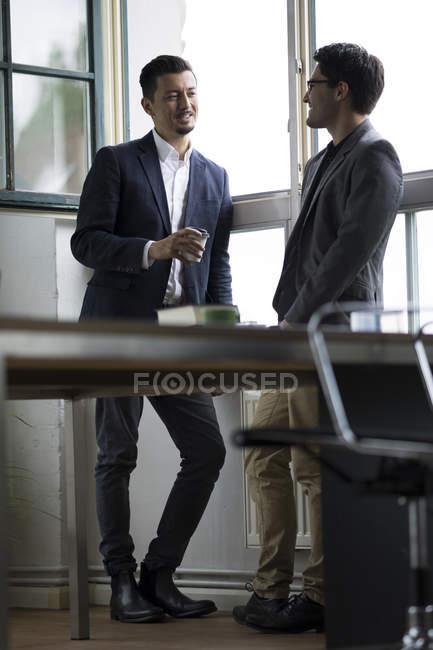 Два предпринимателя, стоя у окна, говорить — стоковое фото