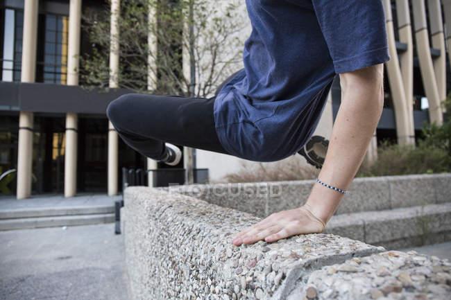 Espanha, Madrid, homem saltando sobre um muro na cidade durante uma sessão de parkour — Fotografia de Stock