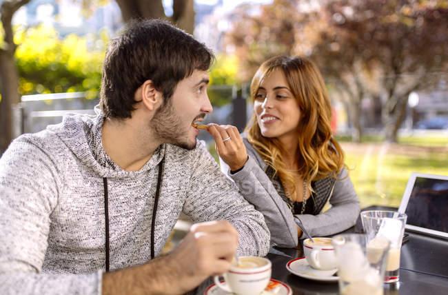 Jovem mulher alimentando seu namorado em um café na calçada — Fotografia de Stock