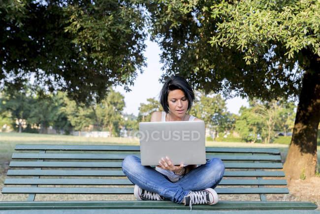 Mujer sentada en un banco en un parque usando un portátil - foto de stock