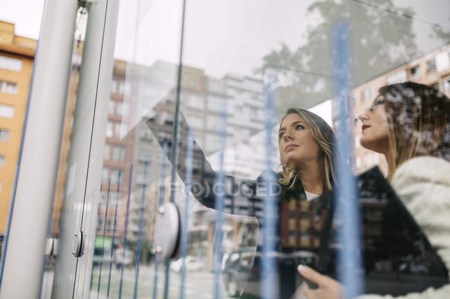 Two businesswomen at city transport stop — Stock Photo