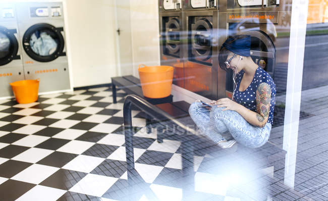 Tattooed young woman hearing music with earbudss in a launderette — Stock Photo
