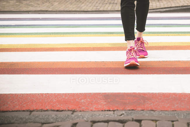 Woman crossing multi coloured zebra crossing, partial view — Stock Photo