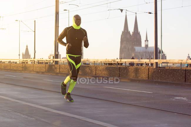 Atleta correndo na ponte com a Catedral de Colônia no fundo, Colônia, Alemanha — Fotografia de Stock