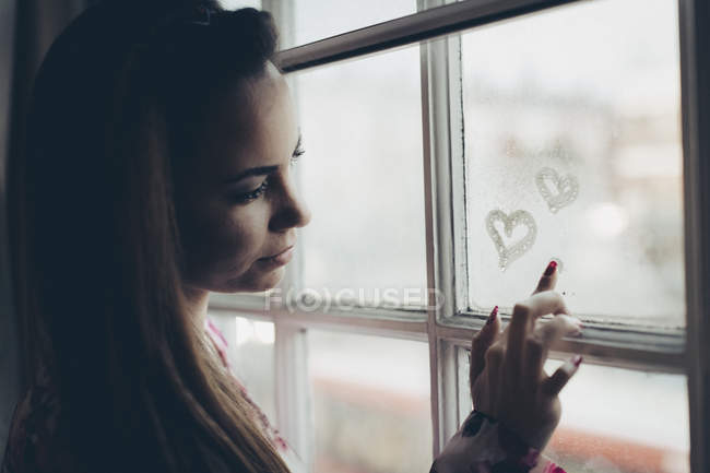 Young woman drawing hearts on fogged-up windowpane — Stock Photo