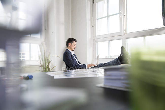 Businessman sitting with feet up and laptop on his lap — Stock Photo