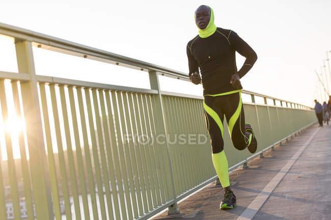 Молодой спортсмен, бегущий по мосту в городе — стоковое фото