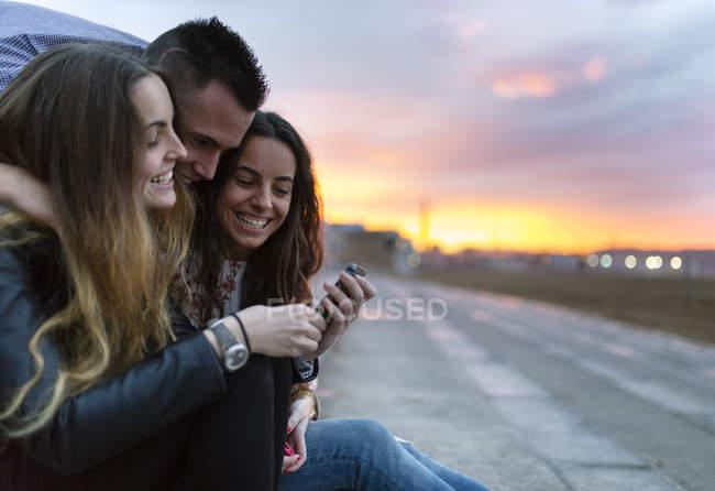 Drei glückliche Freunde in der Abenddämmerung — Stockfoto