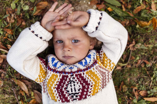 Portrait of pouting blond little boy wearing patterned knit pullover — Stock Photo