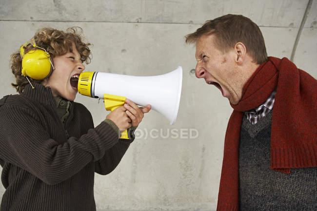 Отец и сын кричат друг на друга магафоном — стоковое фото