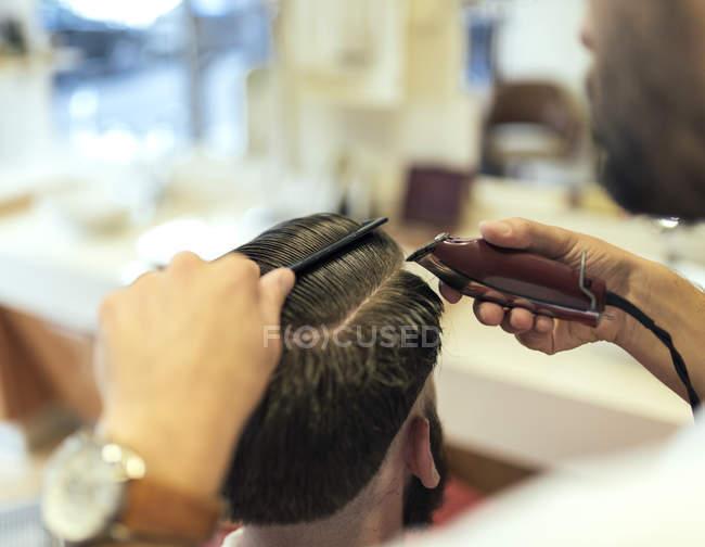 Primo piano del taglio dei capelli da barbiere di un cliente — Foto stock