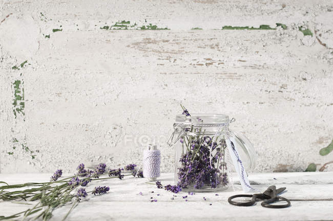 Lavender blossoms in a glass jar, threads and scissors on rustic background — Stock Photo