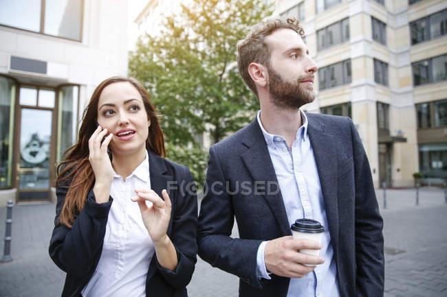 Бизнесмен и деловая женщина с сотовым телефоном и кофе выходят на улицу — стоковое фото