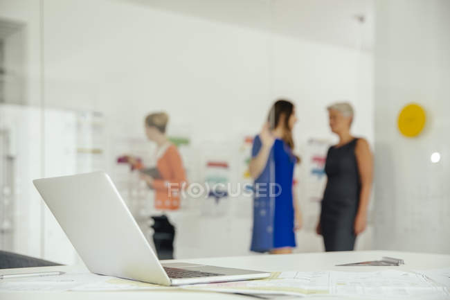 Laptop on desk in office with employees in background — Stock Photo