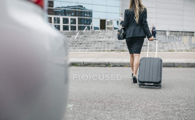 Rear view of businesswoman with suitcase on the move — Stock Photo