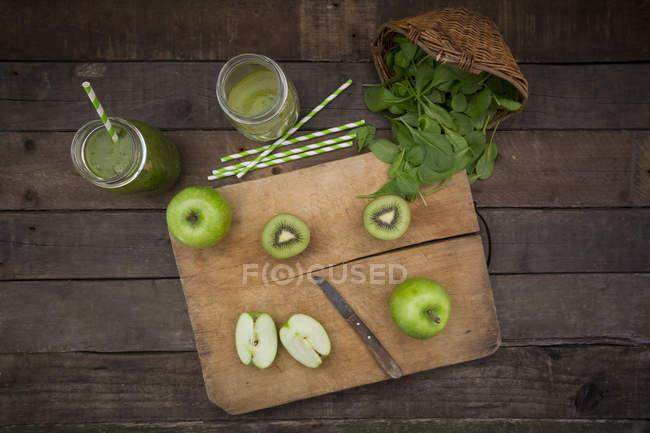 Дві склянки apple ківі пюре зі шпинату і інгредієнтів — стокове фото