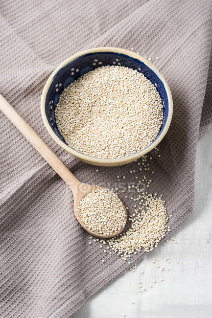 Bowl of quinoa with wooden spoons and kitchen towel — Stock Photo