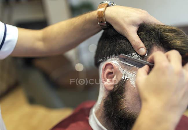 Крупным планом Парикмахерская для бритья бороды заказчика — стоковое фото