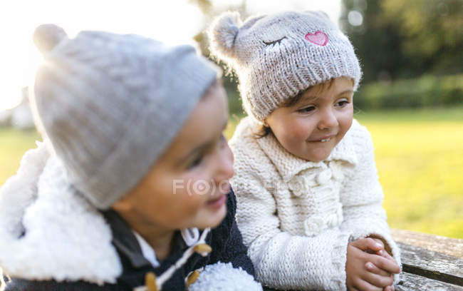 Toddler kids in woolly hats smiling in park — two people 85b60dd9e69