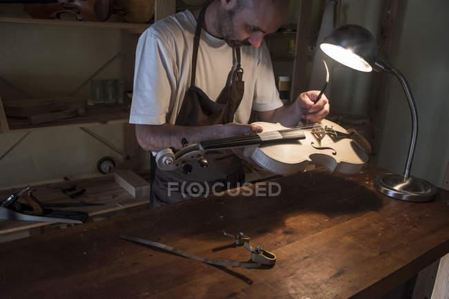 Лютье регулирует звуковой столб скрипки в своей мастерской — стоковое фото