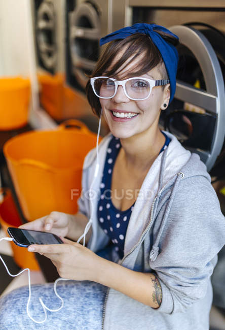 Portrait of smiling young woman hearing music with earbuds in a launderette — Stock Photo