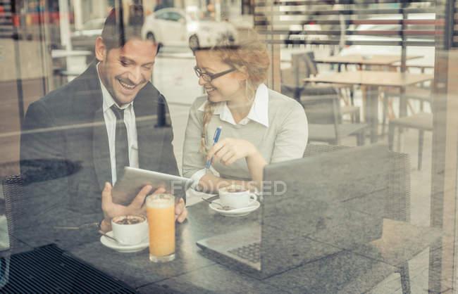 Deux partenaires d'affaires souriants assis dans un café avec tablette numérique et ordinateur portable — Photo de stock
