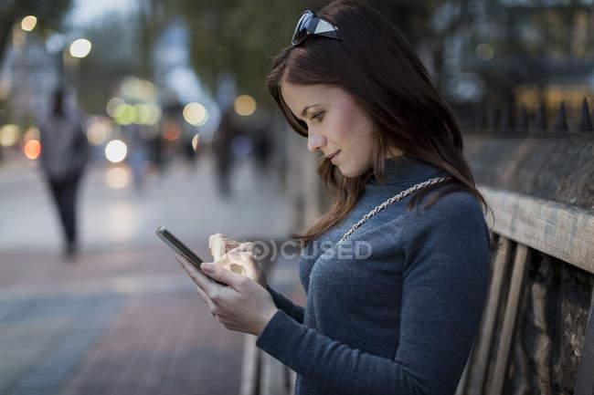 Frau, die Überprüfung von ihrem Smartphone auf einer Bank — Stockfoto