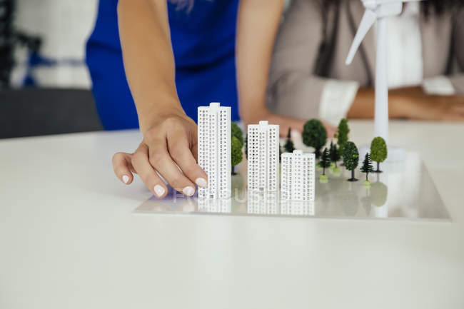 Close-up of hand holding high-rise building model next to wind turbine model on conference table — Stock Photo