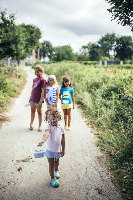 Toddler girl showing plastic box with picked blackberries with friends in background — Stock Photo