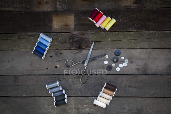 Ciseaux avec boutons et bobines de coton sur bois — Photo de stock