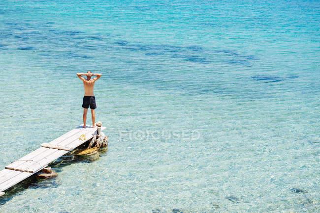 Grécia, Cyclades islands, Amorgos, mar Egeu, homem de pé à beira de um cais de madeira — Fotografia de Stock