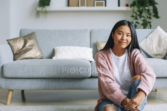 Portrait of smiling young woman sitting on the floor at home — Stock Photo