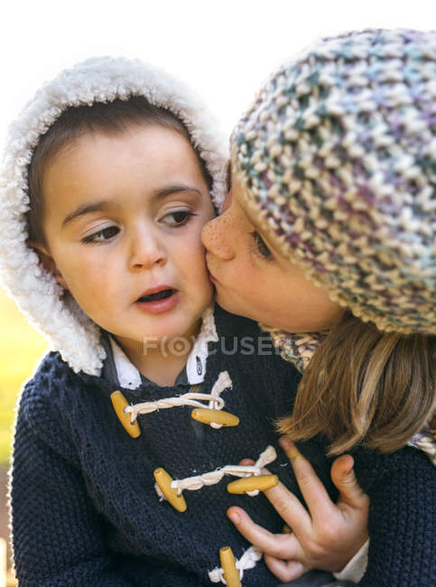 Elementary age girl kissing toddler boy in warm cardigan — Stock Photo