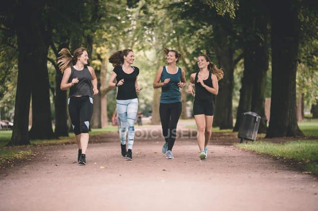 Quatro mulheres sorridentes correndo no parque — Fotografia de Stock