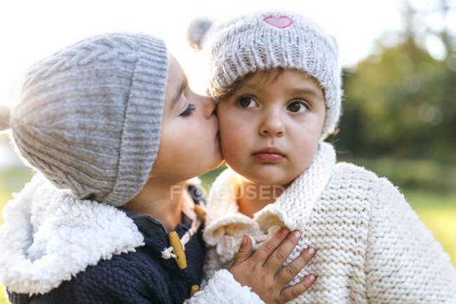 Toddler boy kissing little little girl in woolly hats — Stock Photo