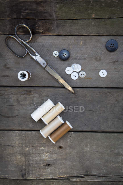 Scissors with buttons and cotton reels on wood — Stock Photo