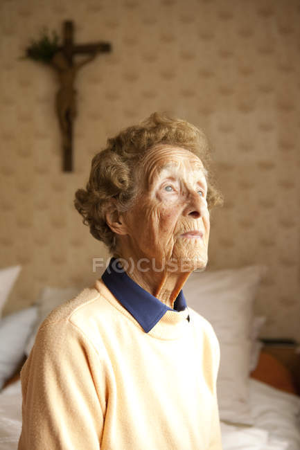 Portrait of aged woman sitting on bed in her bedroom — Stock Photo