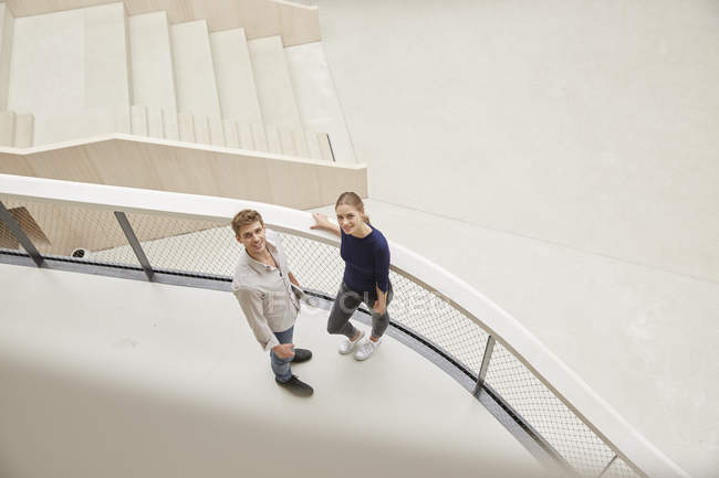 Young man and woman in office building looking up — Stock Photo