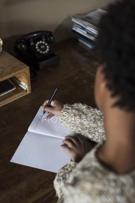 Молода жінка в бюро, писати в Блокноті — стокове фото