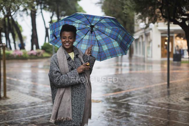Femme souriante avec parapluie un jour de pluie en automne — Photo de stock