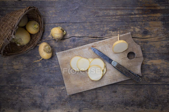 Wicker basket with whole and sliced Swedish turnips, wooden board and a knife on dark wood — Stock Photo