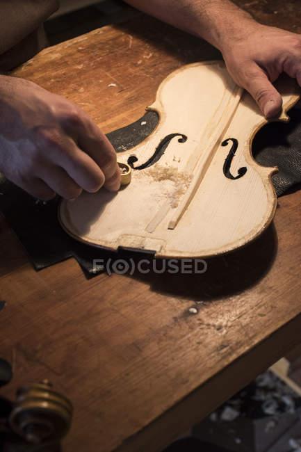Luthier за допомогою міні рука площині на верхній пластині скрипка в його майстерні — стокове фото