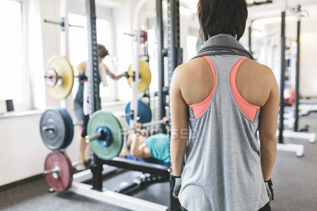 Woman watching two athletes working out in gym — Stock Photo
